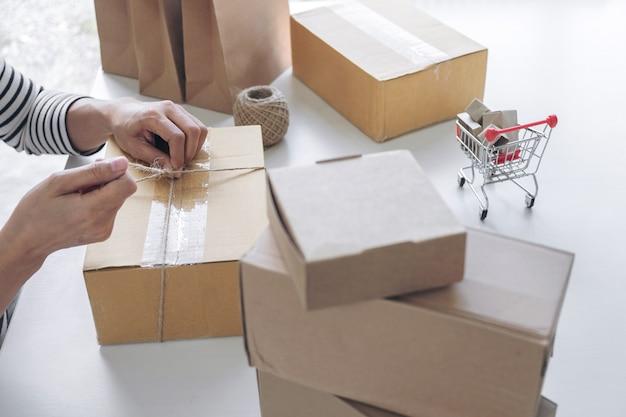 Giovane donna venditore che prepara il pacchetto per spedire la posta
