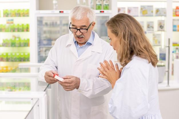 Specialisti giovani e senior che discutono le caratteristiche e l'efficacia di nuovi farmaci o additivi biologicamente attivi in farmacia