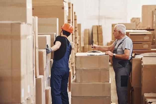 I lavoratori del magazzino giovani e anziani in uniforme lavorano insieme nel magazzino.