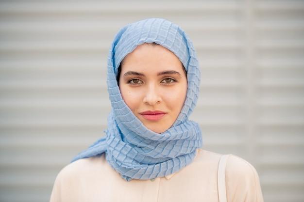 Giovane femmina serena in hijab blu in piedi e ti guarda all'aperto