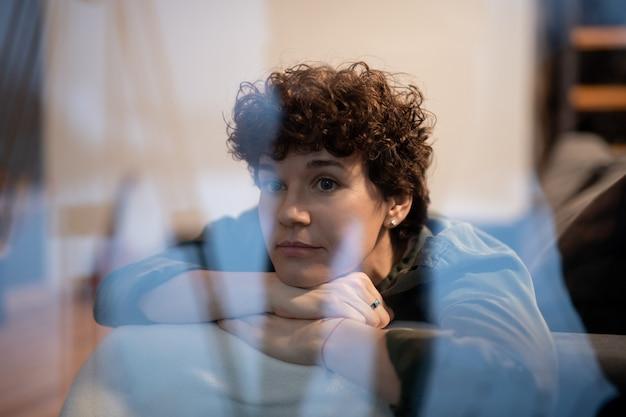 Giovane donna serena in abbigliamento casual che si rilassa sul divano vicino alla finestra nel soggiorno la sera e pensa a qualcosa di piacevole
