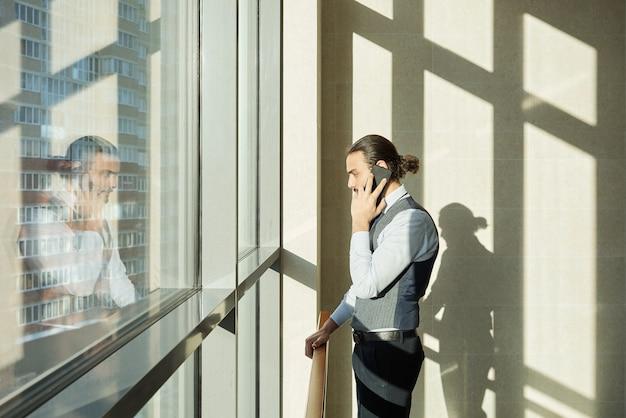 Giovane agente serio o broker in abiti da cerimonia in piedi dalla finestra all'interno di un grande centro business e consulenza ai clienti sullo smartphone