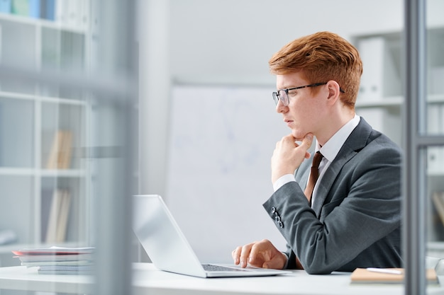 Giovane serio analista in abiti da cerimonia concentrandosi sul lavoro intellettuale davanti al laptop
