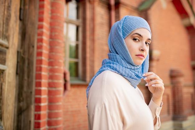 Giovane femmina araba seria in hijab blu che ti guarda mentre fai una passeggiata lungo l'antico tempio