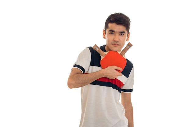 Giovane uomo serio del brunette che gioca ping-pong isolato sulla parete bianca in studio