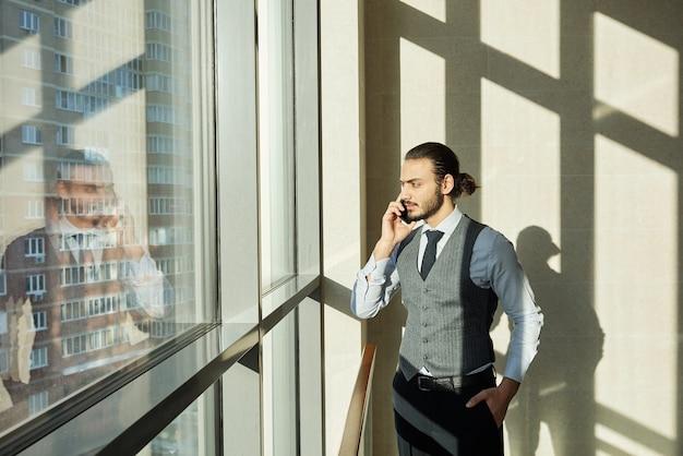 Giovane imprenditore serio guardando attraverso la finestra sulla giornata di sole durante la consultazione di uno dei clienti tramite smartphone il giorno lavorativo