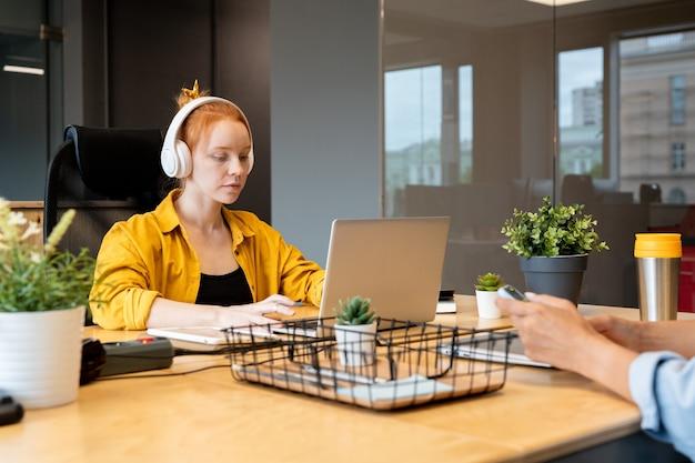 Giovane imprenditrice seria in abbigliamento casual e cuffie che lavorano sulla presentazione per conferenze o seminari davanti al computer portatile