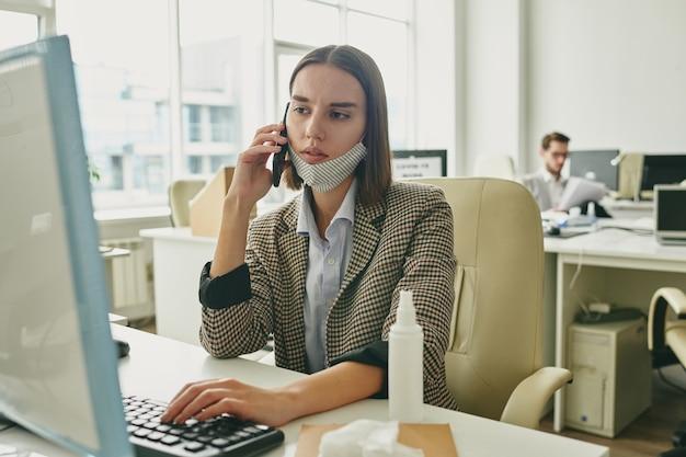 Giovane imprenditrice seria spingendo il tasto della tastiera mentre guarda lo schermo del computer e parla con qualcuno su smartphone al lavoro