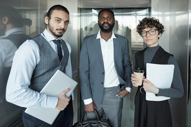 Giovane imprenditrice seria con un bicchiere di caffè e carta e due uomini d'affari ben vestiti interculturali che si muovono in ascensore