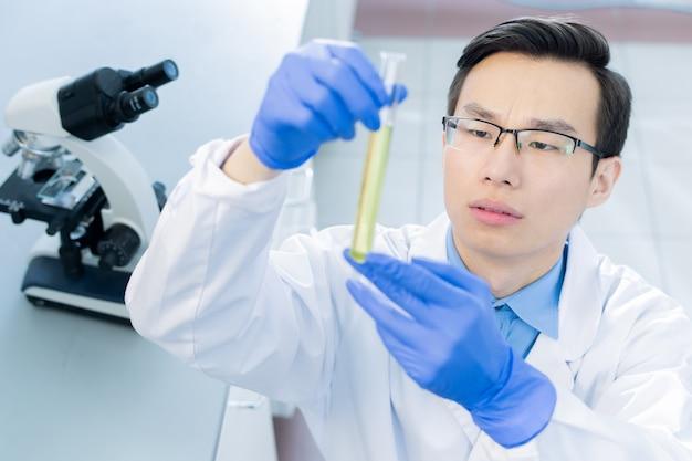 Giovane scienziato cinese serio in whitecoat, guanti e occhiali da vista guardando il pallone con sostanza chimica liquida mentre lo studiava in laboratorio