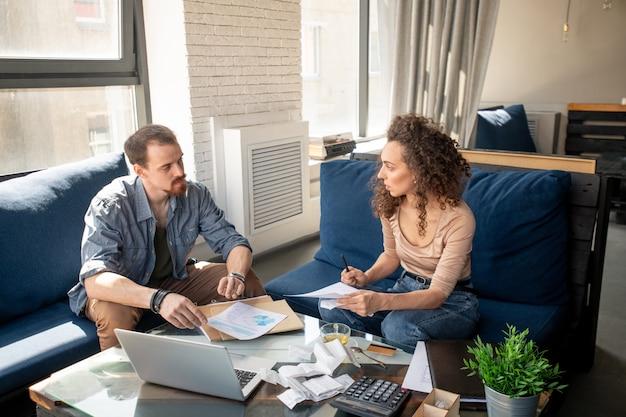 Giovane coppia seria che si consulta sui punti di lavoro e finanziari mentre guarda attraverso i documenti