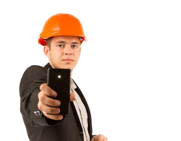 Giovane ingegnere serio che tiene un telefono cellulare nero