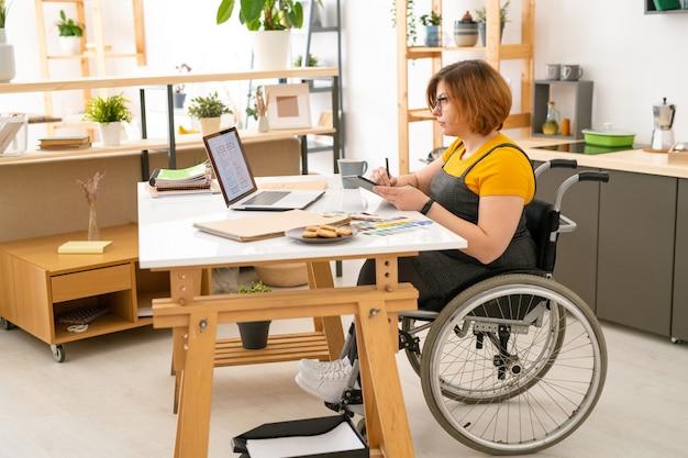 Giovane designer femminile serio in sedia a rotelle che disegna schizzi di nuovi articoli tecnologici con l'aiuto di tablet e stilo a casa