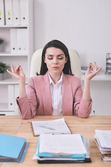 Responsabile di ufficio femminile serio giovane che pratica yoga dalla scrivania pur avendo una pausa dopo il lavoro con documenti finanziari o analizzando i dati