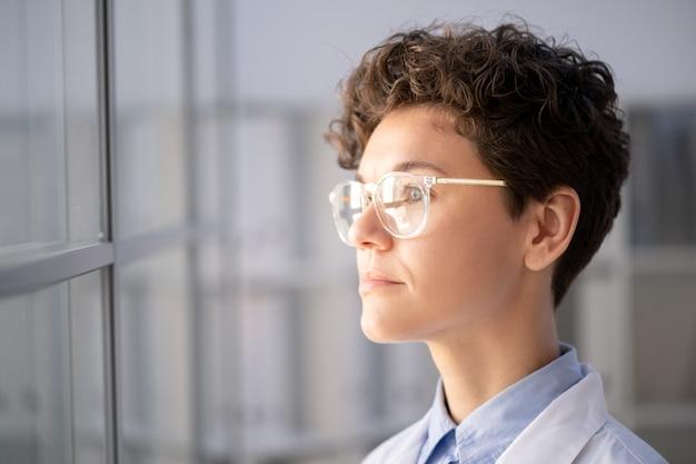 Giovane operaia seria del laboratorio scientifico in whitecoat e occhiali da vista guardando attraverso la parete di vetro