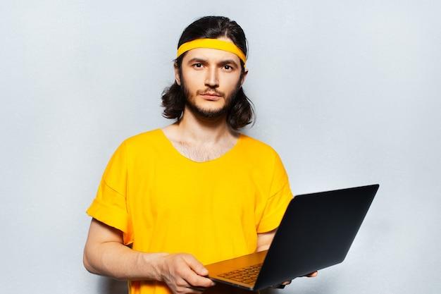 Giovane ragazzo serio con il computer portatile in mano sullo sfondo di uno sfondo grigio. indossa camicia gialla e fascia.