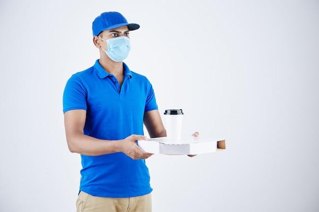 Il giovane corriere indiano serio che dà la scatola della pizza e tira fuori il caffè, isolato su white