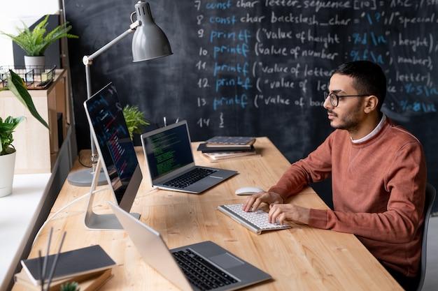 Giovane serio it-manager in occhiali seduto al tavolo davanti al monitor del computer mentre decodifica le informazioni in ufficio