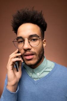 Giovane uomo d'affari serio di razza mista in occhiali e abbigliamento casual intelligente che ti guarda mentre tiene lo smartphone per l'orecchio durante una chiamata di lavoro