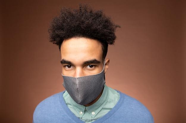 Giovane uomo d'affari serio di razza mista in abbigliamento casual intelligente e maschera protettiva grigia che ti guarda mentre sei in piedi davanti alla telecamera