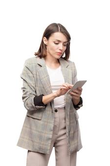 Giovane donna mobile seria in abiti da cerimonia che scorre nel gadget mentre guarda attraverso i contatti