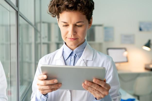 Giovane scienziato serio o chimico in cappotto bianco guardando attraverso le informazioni sullo schermo del tablet mentre si trovava nel laboratorio scientifico