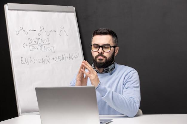 Giovane studente serio in occhiali da vista e abbigliamento casual seduto alla scrivania davanti al computer portatile durante la lezione di chimica online a casa