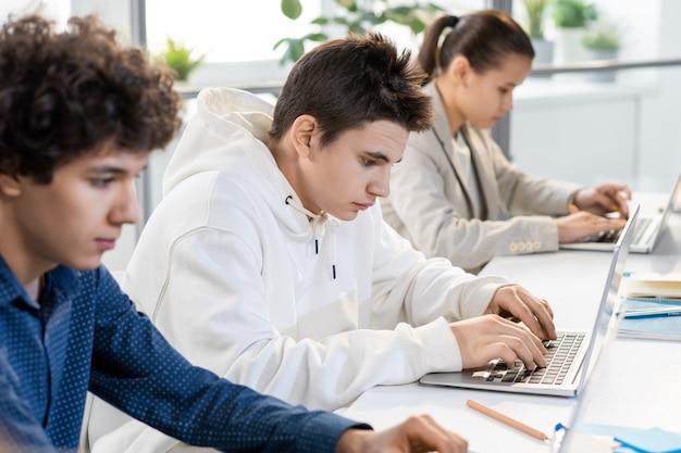 Giovane studente serio guardando i dati sul display del laptop mentre prepara la presentazione del nuovo software tra i compagni di classe