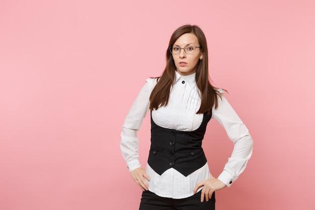 Giovane donna d'affari di successo seria in abito nero, camicia bianca e occhiali in piedi isolato su sfondo rosa pastello. signora capo. concetto di ricchezza di carriera di successo. copia spazio per la pubblicità.