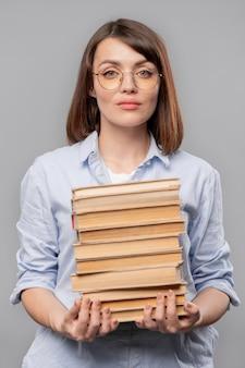 Giovane insegnante serio di letteratura che tiene pila di libri mentre li trasportava per lezione