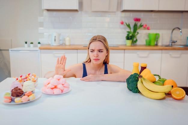 Giovane donna seria in maglietta blu che sceglie fra la verdura della frutta fresca o i dolci nella cucina. scelta tra cibo sano e malsano. dieta. dieta. cibo salutare