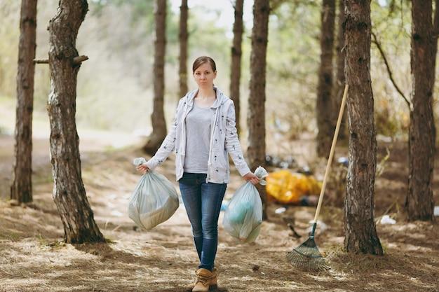 Giovane donna seria in abiti casual che tiene i sacchetti della spazzatura che puliscono i rifiuti in un parco o in una foresta disseminati problema di inquinamento ambientale