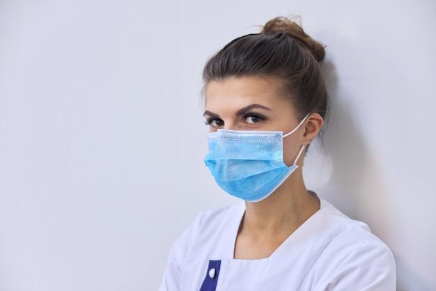 Medico della giovane donna seria nella mascherina medica