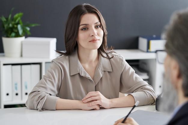 Giovane donna seria in abiti da cerimonia che ascolta il suo consigliere mentre si consulta con lui sui suoi problemi psicologici
