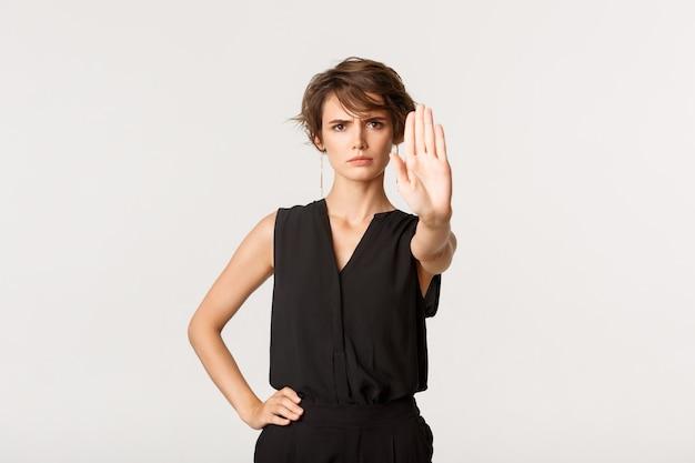 La giovane donna seria dice di fermarsi, dire di no, tendere la mano come mostra il gesto di divieto, in piedi sopra il bianco.