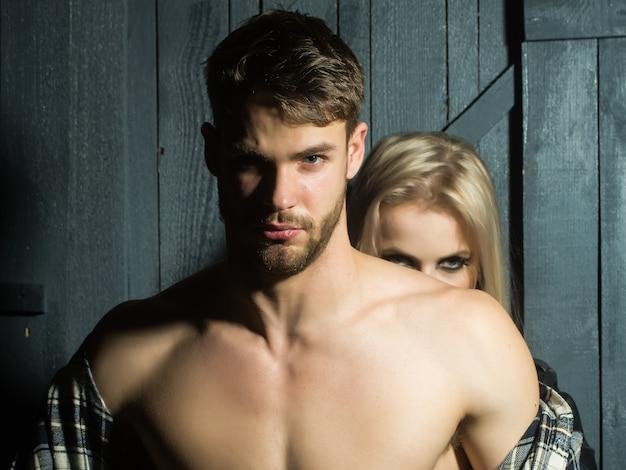 Giovane coppia sessuale di bell'uomo serio in camicia a scacchi con petto muscoloso nudo in piedi davanti a bella donna bionda che abbraccia e tocca il seno in studio, foto orizzontale