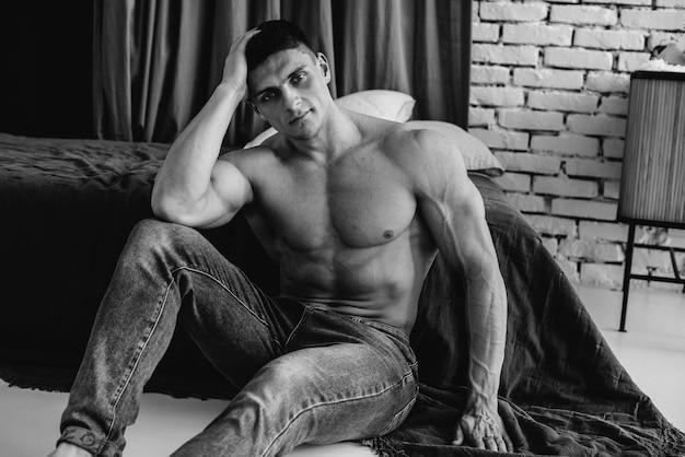 Un giovane atleta sexy con addominali perfetti è seduto su un letto in uno studio in topless in jeans. stile di vita sano, corretta alimentazione, programmi di allenamento e alimentazione per dimagrire. bianco e nero.