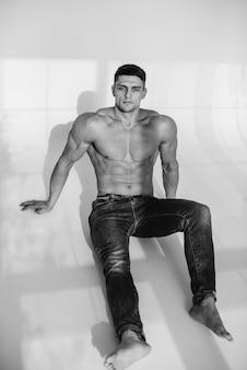 Un giovane atleta sexy con addominali perfetti è seduto in studio in topless in jeans. stile di vita sano, corretta alimentazione, programmi di allenamento e alimentazione per dimagrire. bianco e nero.