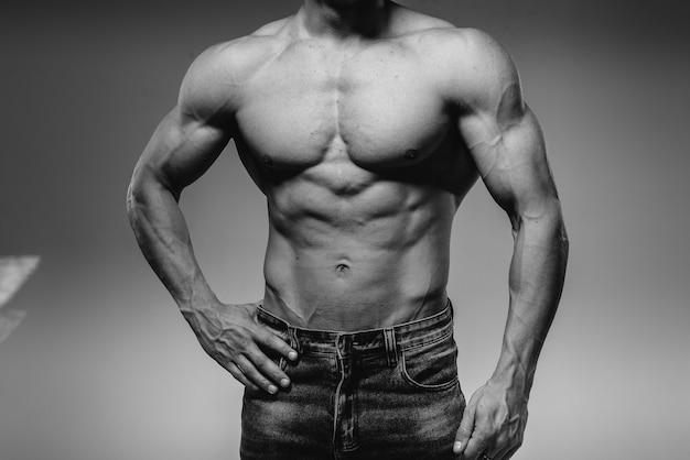 Un giovane atleta sexy con addominali perfetti posa in studio in topless in jeans. stile di vita sano, corretta alimentazione, programmi di allenamento e alimentazione per dimagrire. bianco e nero.