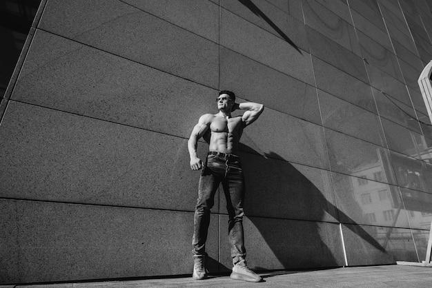 Un giovane atleta sexy con addominali perfetti posa in topless in jeans fuori in una giornata di sole. stile di vita sano, corretta alimentazione, programmi di allenamento e alimentazione per dimagrire. bianco e nero.