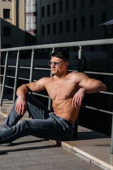 Un giovane atleta sexy con addominali perfetti posa in topless in jeans fuori in una giornata di sole. stile di vita sano, corretta alimentazione, programmi di allenamento e alimentazione per dimagrire.