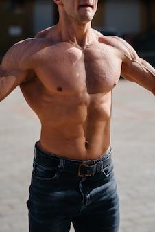 Un giovane atleta sexy con addominali perfetti si allena in topless in jeans fuori in una giornata di sole. stile di vita sano, corretta alimentazione, programmi di allenamento e alimentazione per dimagrire.