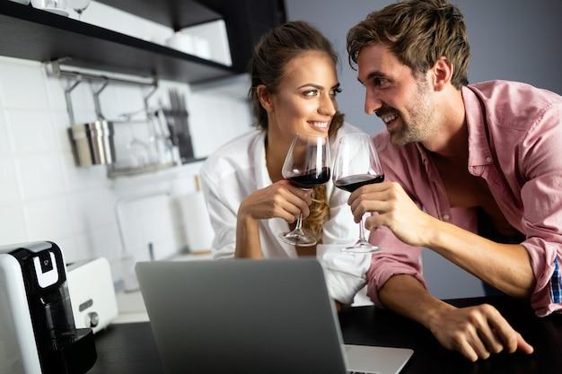Giovane bella coppia sexy che cucina insieme e beve vino