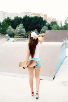 Giovane bella ragazza snella sexy che cammina con lo skateboard in città. hipster ragazza alla moda in un berretto e occhiali da sole.