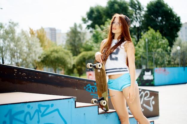Giovane bella ragazza snella sexy con uno skateboard in città. hipster ragazza alla moda in un berretto e occhiali da sole.