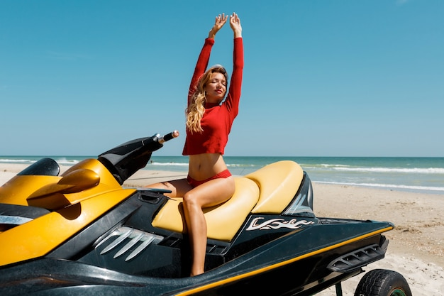 Giovane donna bionda sexy con un corpo perfetto in abito rosso seduto su moto d'acqua sulla spiaggia sotto il sole. week-end estivo o vacanza. sport estremo.