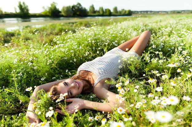 Giovane donna sexy del brunette che si trova sull'erba e sui fiori e che sorride il giorno di estate con la natura verde e fiume al fondo