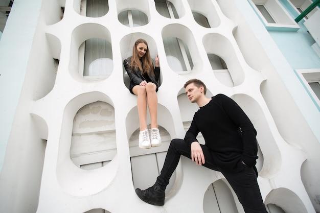 Giovane coppia sexy in abiti neri in posa con uno sfondo sul muro bianco