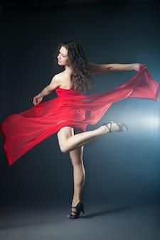 Giovane donna che balla sexy in abito rosso con tessuto con fumo sullo sfondo