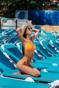 Una giovane ragazza sexy con gli occhiali e un cappello sorride felicemente e prende il sole su un lettino in una giornata di sole. buone vacanze. vacanze estive e turismo.